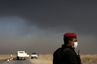 A member of the Iraqi special forces guards a checkpoint near the village of Awsaja, Iraq, as smoke fills the air.  Photo / AP