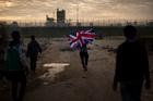 A man runs with a British flag inside a makeshift camp known as the Jungle near Calais, northern France. Photo / AP