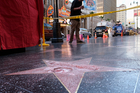 A man stands near a cordoned off area surrounding the vandalised star for Republican presidential candidate Donald Trump on the Hollywood Walk of Fame in Los Angeles. Photo / AP