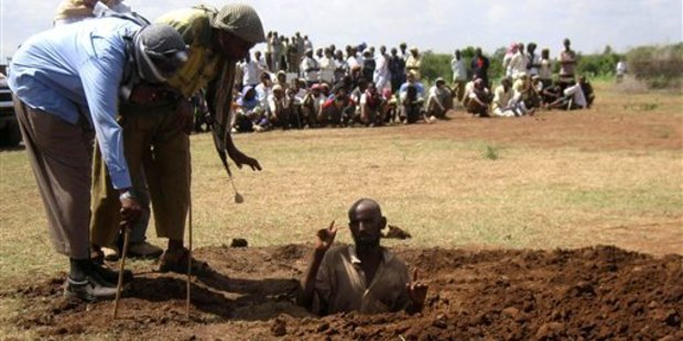 A man is buried in the ground before being stoned to death by militants from the Hizb Al-Islam group in Afgoye, a district Somalia in December 2009. Photo / AP