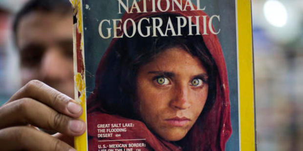 Pakistan's Inam Khan, owner of a book shop shows a copy of National Geographic magazine with the photograph of Afghan refugee woman Sharbat Gulla, from his rare collection. Photo / AP