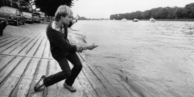 Circa 1979: Sting, lead singer and bass player with the pop group The Police, relaxes by skimming stones by the riverbank at Putney, south west London. Photo / Getty