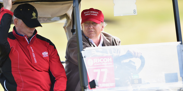 Republican Presidential Candidate Donald Trump drives a golf buggy on a golf course Turnberry on July 30, 2015. Photo / Getty