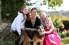 Kelleigh Burkett with her three children Paige, 11, with scarf, Holly, 9, in white and Charli, 7, in pink with dog Jade at their North Shore home. Photo / Getty Images