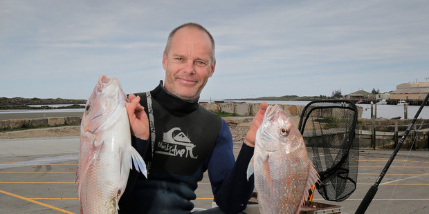 Rob Chamberlain holds two snapper caught from his jetski. PHOTO/ BEVAN CONLEY
