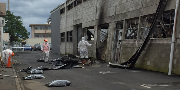 Asbestos removal workers at AH Franks Tyres on Tuesday. The worker on the right stands next to where Sunday's arson occurred, which is also near where Monday's fire started. Photo / Belinda Feek