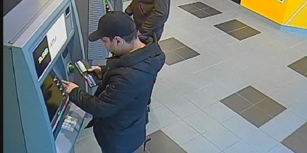 Bogdan Irimia (bottom) caught on camera using skimmed cards at an ATM. Photo / Supplied.
