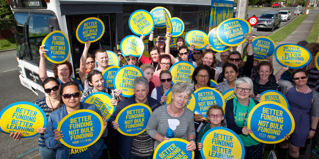 Loading CAMPAIGN: Members of the better funding bus tour and Lynmore School staff showed off their campaign signs. PHOTO/STEPHEN PARKER