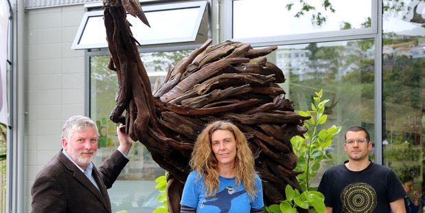 From left, Mike Dickison, Rachael Garland and Jack Marsden-Mayer with the giant driftwood sculpture. PHOTO/STUART MUNRO