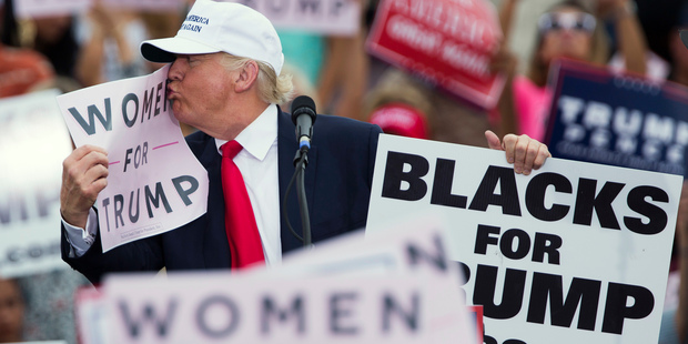 Republican presidential candidate Donald Trump kisses a sign during a campaign rally. Photo / AP