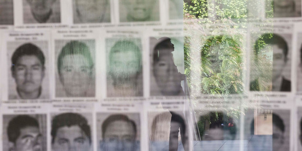 A university student is reflected in a glass display case showing the photos of 43 missing students from the Rural Normal School of Ayotzinapa, Mexico. Photo / AP