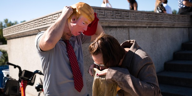 Ben Arnold, left, and his wife Melissa Arnold, 34, of Marietta, Ohio, put on their Donald Trump and Hillary Clinton masks on in front of the Lincoln Memorial.