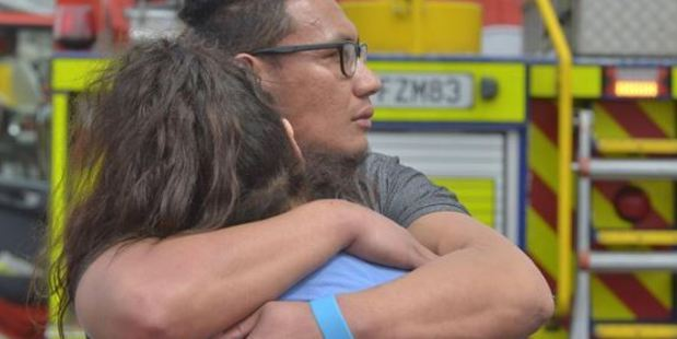 A couple console each other after escaping a fire which tore through their Dunedin flat yesterday. Photo / Otago Daily Times