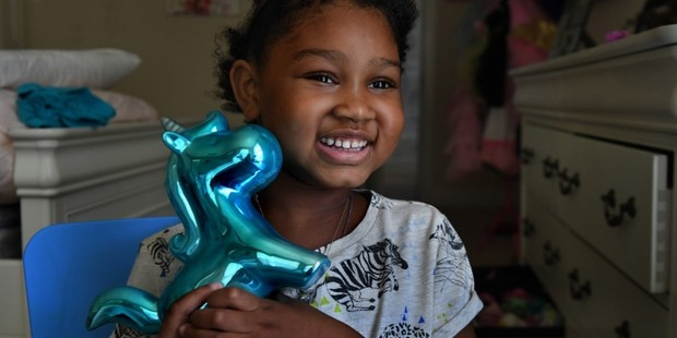 Eden Oyelola, in an August photo, holds a unicorn coin bank that was given to her by the Make-a-Wish Foundation. Photo / The Washington Post