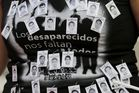 A protester takes part in a march in Mexico City last year, calling for justice for 43 missing students. Photo / Supplied