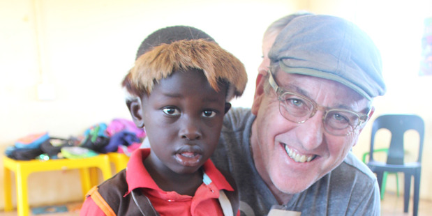 John Elliott with a child from a school in South Africa who has benefited from the buy-one-give-one policy of his company, TOMS. Photo / Supplied