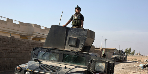 An Iraqi special forces soldier stands atop a Humvee in the village of Bazwaya, some 8km from the centre of Mosul. Photo / AP
