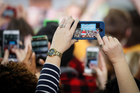 An attendee takes a cellphone photo of Democratic presidential candidate Hillary Clinton as she speaks during a campaign rally at Kent State University, Ohio. Photo / AP