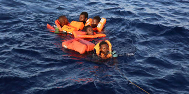 Migrants who fell in the water from a crowded rubber dinghy are rescued. Photo / AP