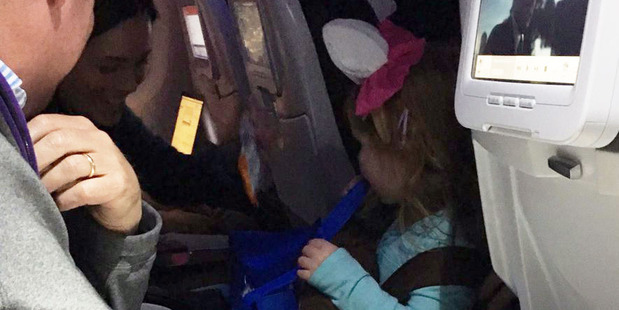 The little girl walked around the plane collecting treats from other passengers. Photo / Stephanie Kahan