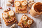 Natural peanut butter on wholemeal toast, using two tablespoons of the spread and topping with a banana and a sprinkle of cinnamon is a recommended breakfast. Photo / Getty