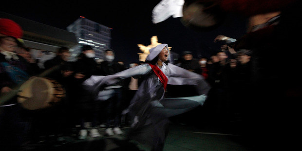 A protester satarises President Park's relationship with a sector's daughter Choi Soon-Sil wearing a costume of a shaman during a protest in Seoul. Photo / Getty