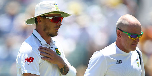 Dale Steyn of South Africa walks from the field with the team physio after injuring his shoulder. Photo / Getty