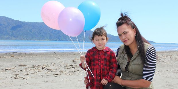 Tara Maniapoto with daughter Alexus Knott, 3, at Paraparaumu Beach, where a community vigil will take place this Friday evening for two silblings who died in Perth. Photo: Cloe Willetts.