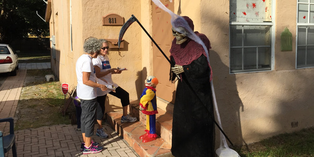 Loading The Grim Reaper guards a house in West Palm Beach as Clinton campaign volunteers Susan Lemkin (left) and Amy Arlein go knocking.  Photo / Chris Reed