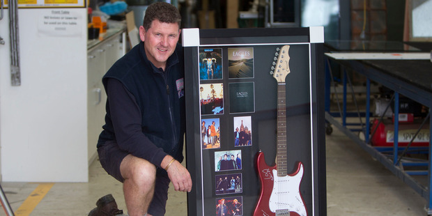 Loading MEMORABILIA: Auction leader Chris Smith with the signed and framed Eagles guitar for the Rotary Rotorua Charity Luncheon. PHOTO/BEN FRASER
