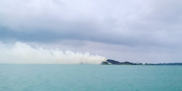 Smoke trailed across the water from the fire on Browns Island. Photo / Aya McKenzie