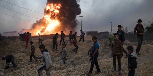 Children play next to a burning oil field in Qayara, south of Mosul, Iraq. Photo / AP