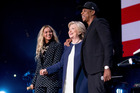Hillary Clinton, center, appears on stage with artists Jay Z, right, and Beyonce, left, during a free concert at at the Wolstein Center in Cleveland. Photo / AP