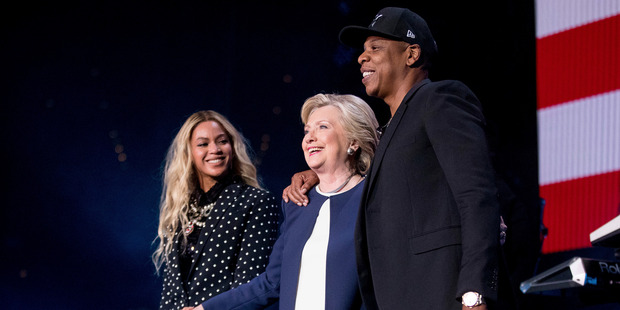Democratic presidential candidate Hillary Clinton, center, appears on stage with artists Jay Z, right, and Beyonce, left, during a free concert. Photo / AP