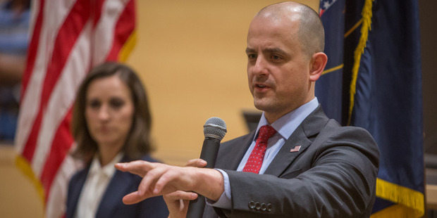 Evan McMullin answers questions from voters at a town hall meeting at the Syracuse City Hall in Utah. On the left is his running mate, Mindy Finn. Photo / AP