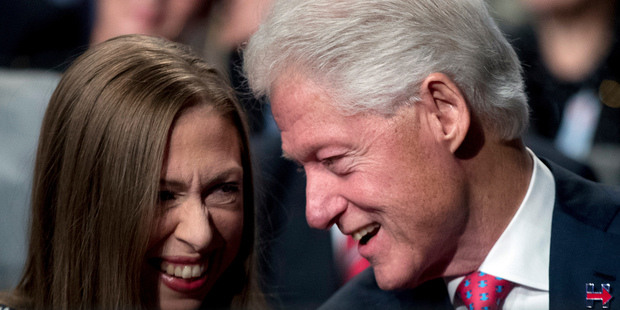 Former President Bill Clinton, right, speaks to his daughter Chelsea. Photo / AP