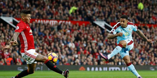 Burnley's Andre Gray, right, has a shot blocked by Manchester United's Marcos Rojo battle for the ball during their English Premier League soccer match. Photo / AP.