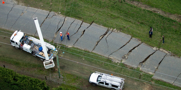 Linesmen prepare to repair damaged power lines along a cracked-open road at Darfield following the 7.1 quake that struck near there in September 2010. Photo: File