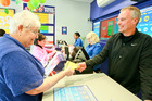 Lotto player Langia Hill buys a ticket from  Andrew Spence, owner of Andrew Spence Pharmacy. Photo Warren Buckland