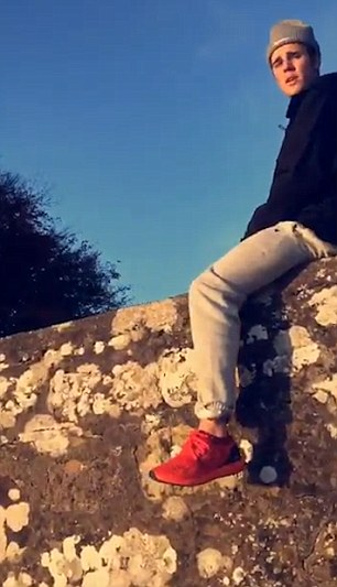 Justin Bieber sitting on a wall in Scotland.