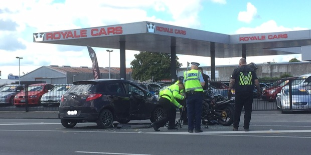 Tow truck staff and police lift up the motorbike and prepare for it to be taken away after the bike and a car collided on Greenwood St, Hamilton, today.