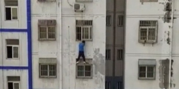 Loading Liang Lei scaled several storeys to reach the struggling two-year-old boy. Photo / Youtube / CCTV