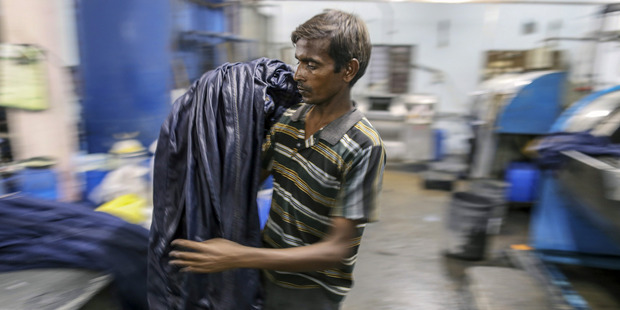 A worker unloads jeans from a fabric dyeing machine at a factory in the Mundargi Industrial Area of Ballari, Karnataka, India, on May 16, 2016. Bloomberg photo by Dhiraj Singh