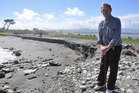 Colin Growcott, who worked on building the Hokitika River rockwall to replace the old wharf in the 1960s, looks over the erosion at the Hokitika spit. Photo / Hokitika Guardian