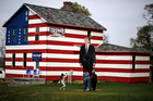 A young visitor takes a photo of a giant cutout of Republican candidate for president Donald Trump in front of the Trump House owned by Lisa Rossi in Youngstown, Pennsylvania. Photo / AP