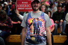 A man wears a tank top depicting Republican presidential nominee Donald Trump standing on a tank during a campaign rally for Trump. Photo / Getty