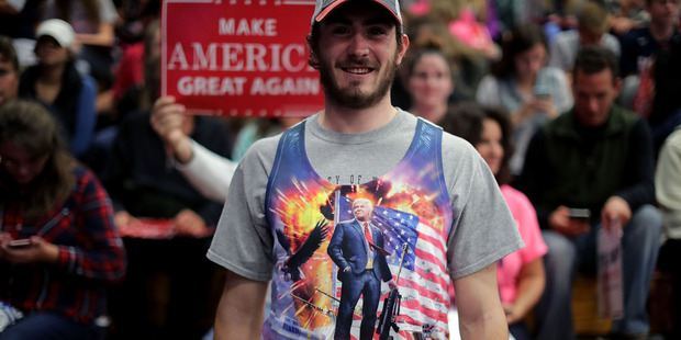 Loading A man wears a tank top depicting Republican presidential nominee Donald Trump standing on a tank during a campaign rally for Trump. Photo / Getty