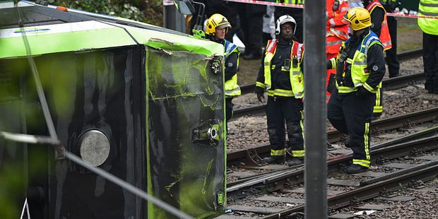Members of London Fire Brigade look at the overturned tram at the site near Sandilands Tram stop in Croydon. Photo / Getty