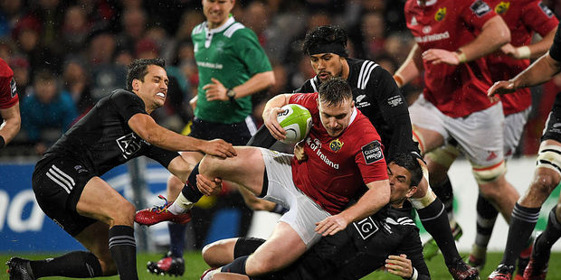 Rory Scannell of Munster is tackled by Tim Bateman, left, and Otere Black of Maori All Blacks. Photo / Getty Images
