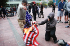 Anti-Trump protests at Aotea Square Auckland today. Pictured is a protestor burning an American flag. Photograph by Doug Sherring